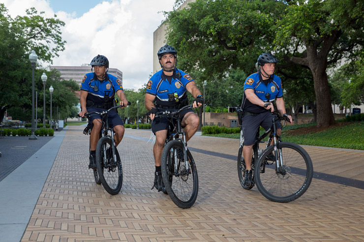 officer group on bike patrol through brick paved speedway on UT campus