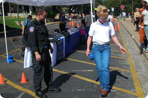 woman tries to walk on a line with goggles while officer watches