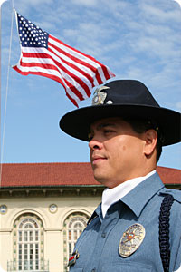 Officer Riojas in Honor Guard uniform in front of U.S. flag at half-mast